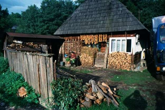 Typical farm house with steep roof, woodpiles, drying peppers, cook cleaning vegetables.