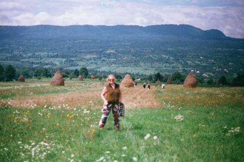 Hiking through haystack-dotted meadows, Kate not hidden by camouflage pants